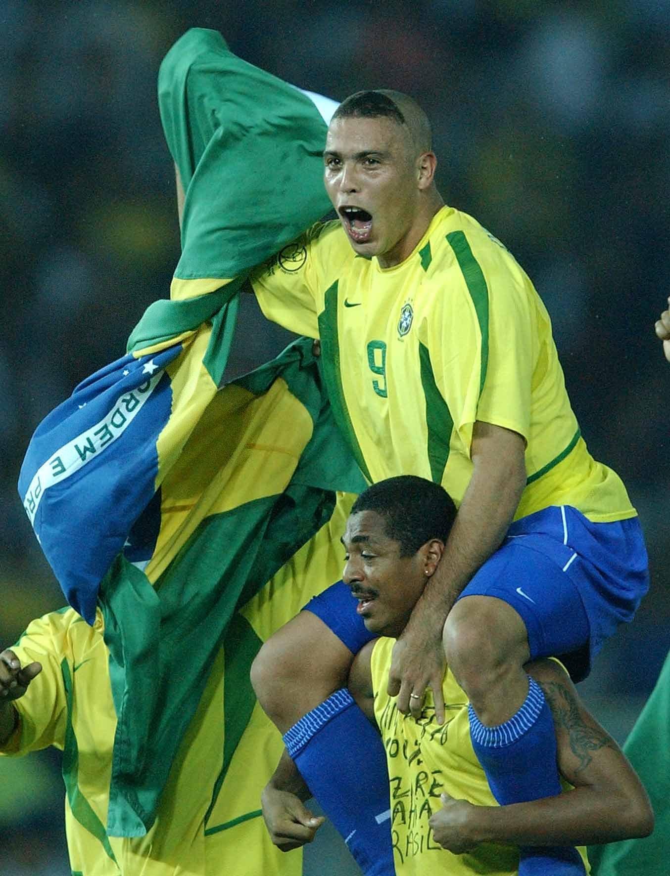 """2002年世界杯决赛前,正当人们担心罗纳尔多是否会像四年前一样迷失在决赛赛场上时,""""外星人""""以一个全新发型亮相,一扫四年前法兰西大球场的阴霾,在决赛中打入两球帮助巴西队战胜德国队,第五次捧起大力神杯。这个发型被中国球迷戏称为""""阿福头""""。\\\\r\\\\n图为2002年6月30日,巴西队球员罗纳尔多(上)与队友在世界杯颁奖仪式上庆祝夺冠。"""