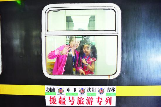"""左图:游客在即将发车的""""援疆号旅游专列""""上与亲人挥手告别。 张扬 摄"""