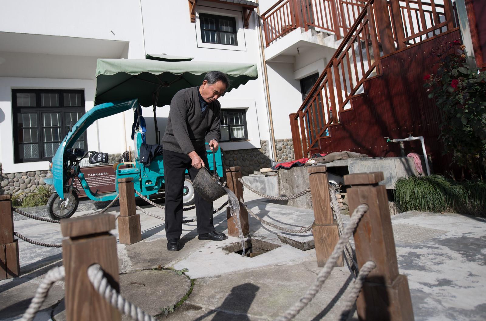 下姜村村民姜祖海给自家沼气池添水(1月10日摄)。新华社记者 翁忻旸 摄