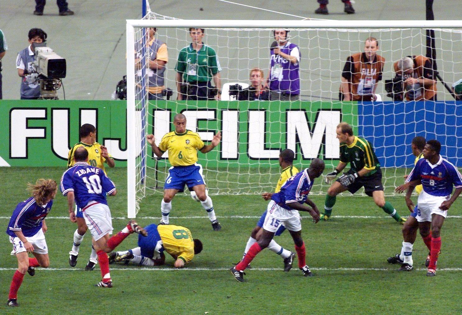 图为1998年7月12日,在法国世界杯决赛中,巴西队门将塔法雷尔(右三)在比赛中未能阻拦法国队球员齐达内(前左二)的头球攻门。