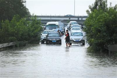 昨日,五环路化工桥下匝道处,有小汽车因积水无法通行,有车主下车查看水深。新京报记者 侯少卿 摄