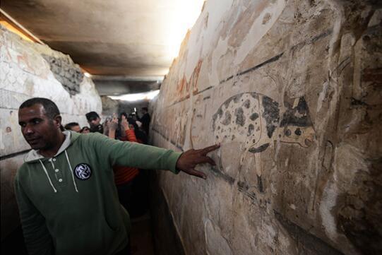 """""""图为资料图片,显示了埃及古物部导游站在古王国时期女祭司海特佩特古墓内的壁画前进行讲解。图片来源:法新社/穆罕默德?埃尔?沙赫德。"""
